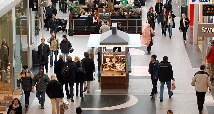 En bild från ovan inne i ett köpcentrum. Några affärer synd. En bred gång mellan dem där ganska mycket människor går. I bakgrunden är ett café.