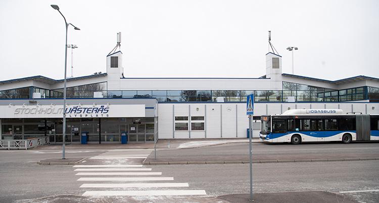 Ett vitt övergångsställ över gatan och på andra sidan syns entrén till flygplatsterminalen.