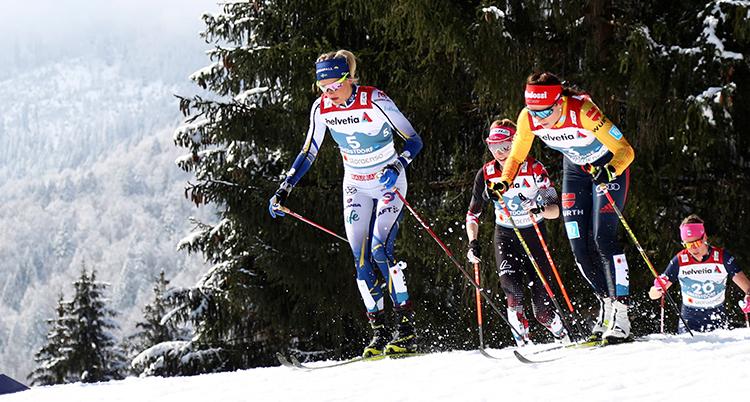 Fyra åkare synd lite på avstånd. Frida Karlsson är första av dem Hon har vit och blå dräkt och ett blått pannband. Det synd att de är uppe på ett berg. En dal syns bakom dem.
