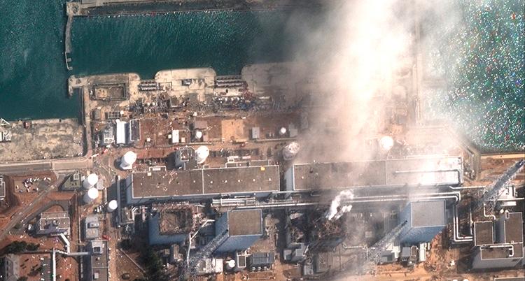 Ånga stiger från kärnkraftverket som syns från luften intill havet.