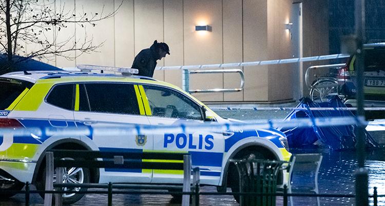 En polisbil syns. Det är mörkt. En polisman syns bakom bilen.