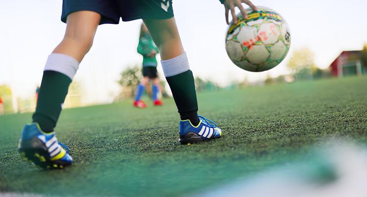 En person med fotbollsskor är på väg att skjuta ut fotbollen på fotbollsplanen.