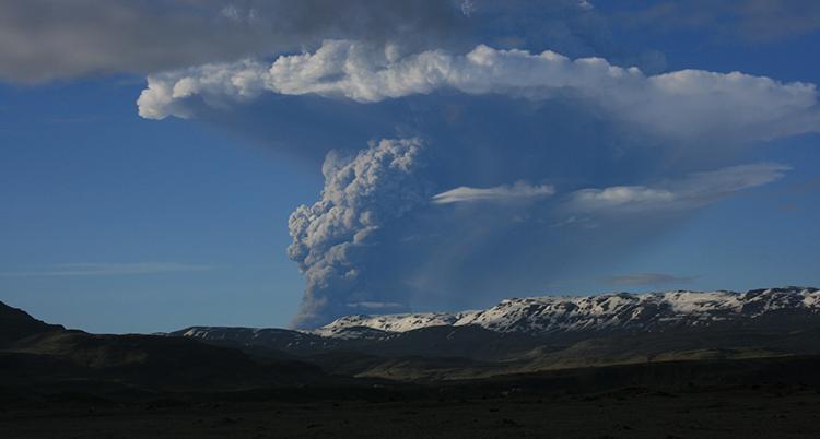 Rök kommer upp från en vulkan. Himlen är blå.