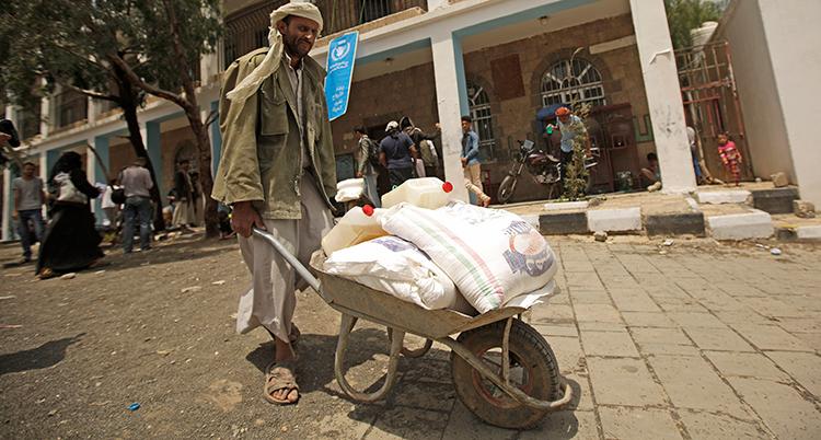 En man går med en skottkärra med säckar i.