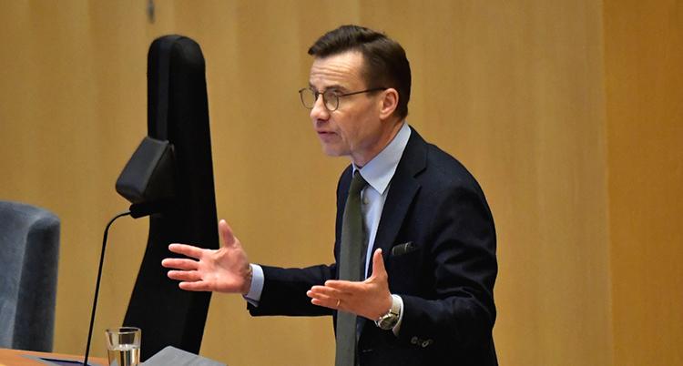 Kristersson står vid en mikrofon. Han är mitt i ett tal och slår ut med armarna. Han är engagerad.