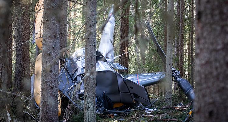 En helikopter ligger på marken i skogen. Den är helt förstörd.