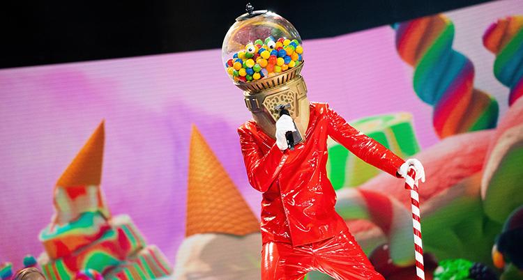 En person i röd kostym och med en godisautomater som mask över huvudet står på en färgglad scen och sjunger i en mikrofon medan den stödjer sig mot en polkagrisrandig käpp i vänster hand