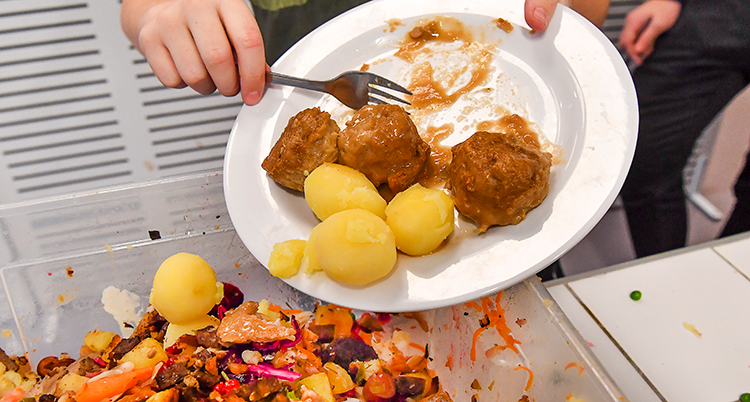 En hand som skrapar av mat från en vit tallrik ner i en skräpkorg.