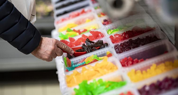 En hand håller i en spade. Den plockar godis ur lådor.