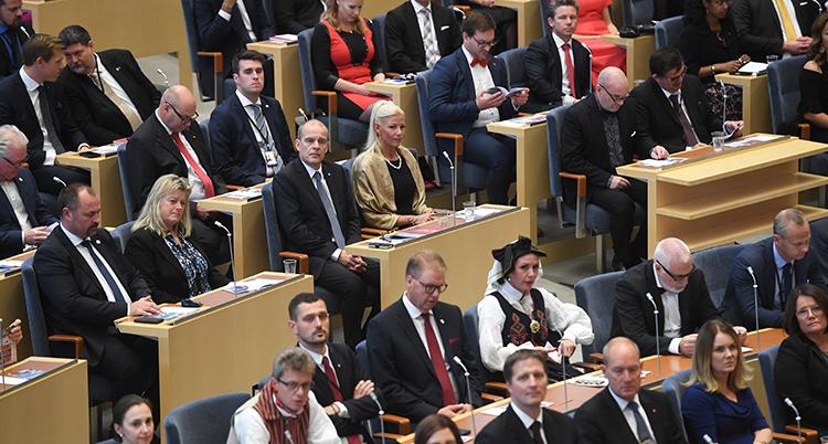 Politiker i riksdagen sitter i sina bänkar