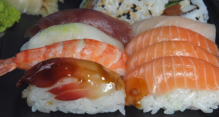 Flera bitar sushi ligger upplagda, de är gjorda av vitt ris med lax ovanpå.