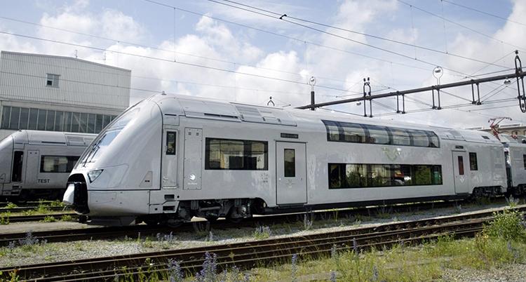 Ett tåg i grå blank färg. Man ser den första vagnen . Den har två våningar och man ser två rader med fönster.