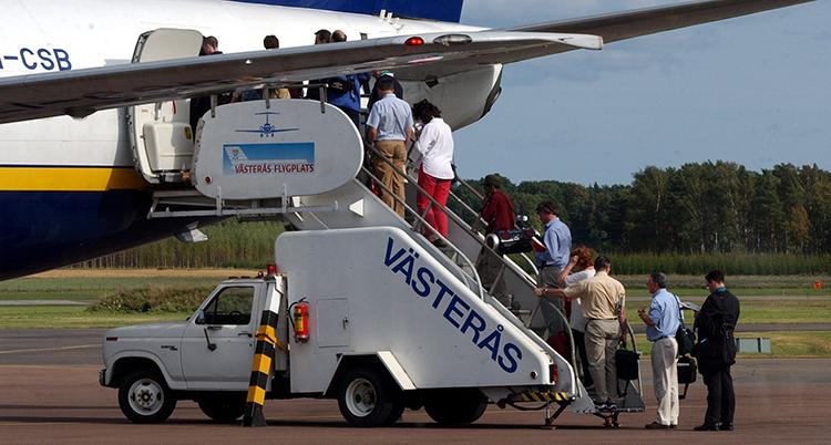 Människor går ombord på ett flygplan med hjälp av en trappa på flaket på en bil.