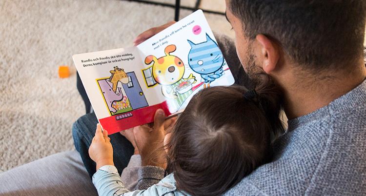 En pappa fotad bakifrån läser för sitt barn i knät.