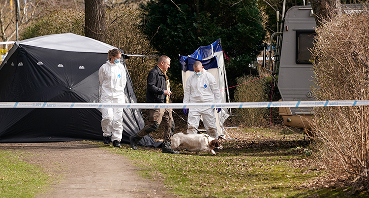 Poliser i vita overaller bakom en avspärrning utomhus.
