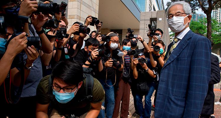 En äldre man i munskydd och välstruken blå kostym blir fotad utanför domstolen av massor av pressfotografer.
