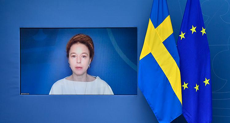 Amanda Lind pratar på en stor videoskärm. Bredvid skärmen finns en svensk flagga och EUs flagga.