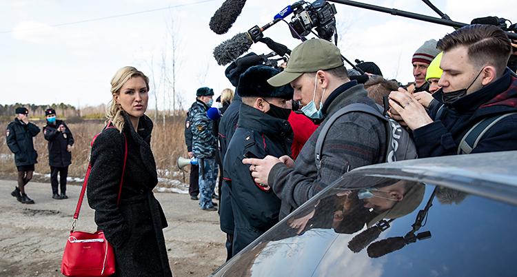 En blond kvinna står på en väg. Flera journalister filmar henne och intervjuar henne. I bakgrunden står några poliser.