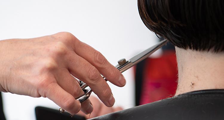 En närbild på en hand som håller i en sax. Handen klipper håret på en person som har mörkt hår.
