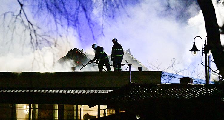 Det är kväll. Två brandmän står på ett tak. De försöker släcka en brand. Det är mycket rök.