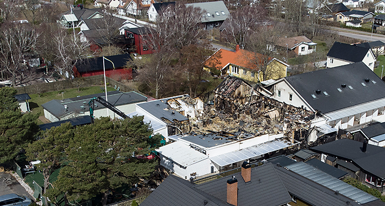 En bild som är tagen uppifrån. Det visar taken på flera hus. Ett av husen är mycket skadat efter en brand.
