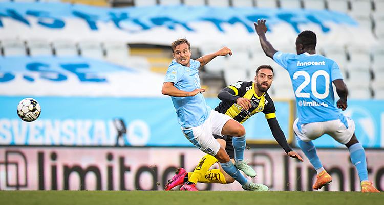 Från en match i fotboll. Tre spelare kämpar om bollen. Två av spelare har blå tröjor. Den tredje spelaren har en tröja som är gul och svart.