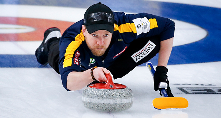 Bilden är från en match i curling. Vi ser Niklas Edin på bilden. Han ligger på isen och siktar med en sten. Han har en keps på huvudet.