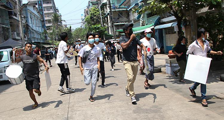 Bilden är från en stad i landet Myanmar. Människor springer på en gata. De springer mot kameran. Flera har munskydd på sig.