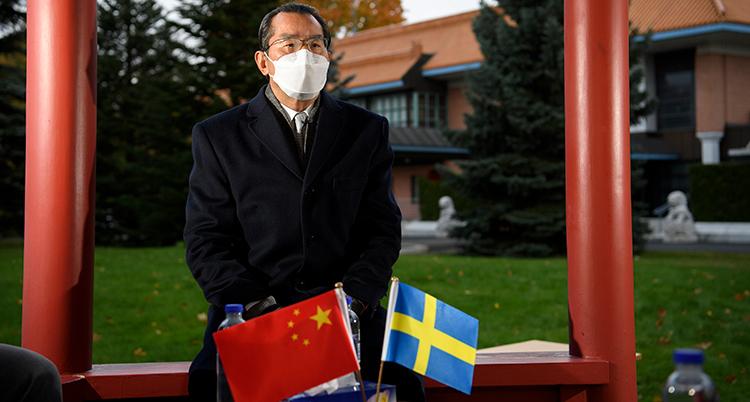 Ambassadören framför två små flaggor. En svensk flagga och en kinesisk.