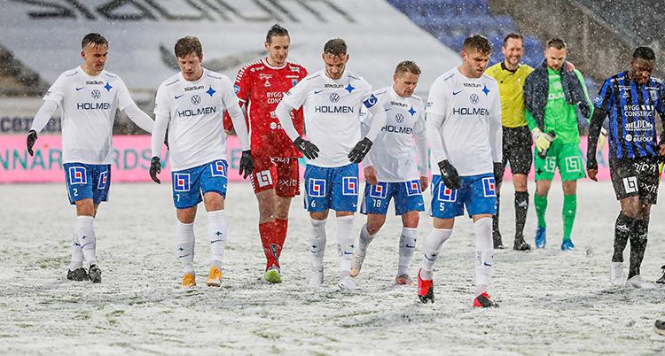 Från en match i fotboll. Matchen är slut. Spelarna är på väg av planen. Det snöar. Och det ligger snö på planen.
