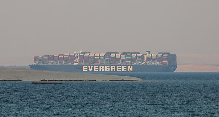 Ett stort fartyg står stilla vid en strand. Fartyget är lastat med flera tusen stora lådor, containrar.