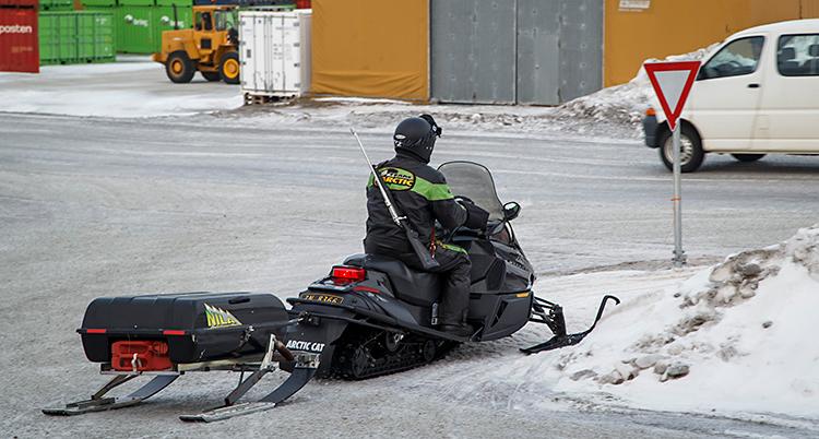 Bilden är tagen i Longyearbyn på Svalbard. Vi ser en skoter som kör på en vanlig väg.