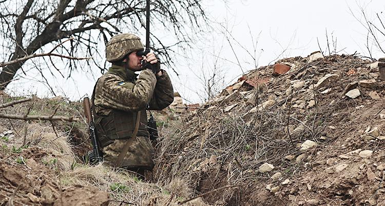 En soldat står i en skyttegrav. Han tittar i kikare. Han har på sig kläder i kamouflage. Han har en hjälm och ett gevär.