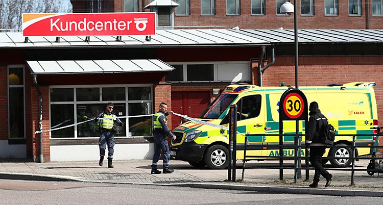En bild som är tagen utomhus, i Linköping. Två poliser står vid ett avspärrningsband. En ambulans står bredvid. Bakom finns ett hus där det står Kundcenter på taket.