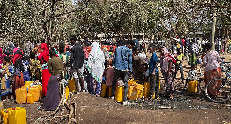 En grupp med människor står utomhus. De ska hämta vatten. De har gula dunkar som de hämtar vatten i.