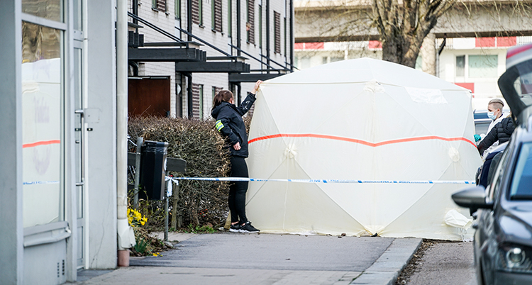 Poliser på ett gata med ett stort uppfällt vitt skynke eller tält.