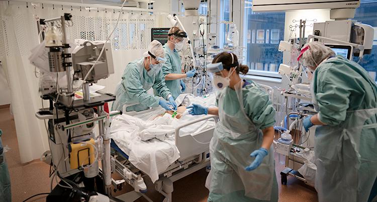 Från ett rum på sjukhus. Fyra personer jobbar. De har skyddskläder och skydd för ansiktet. På sängen ligger en patient. Patienten är skymd, så ansiktet syns inte.