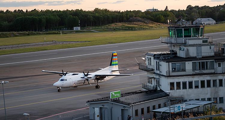 En bild från Bromma flygplats. Vi ser byggnaden. I bakgrund finns en bana. Där står ett flygplan.