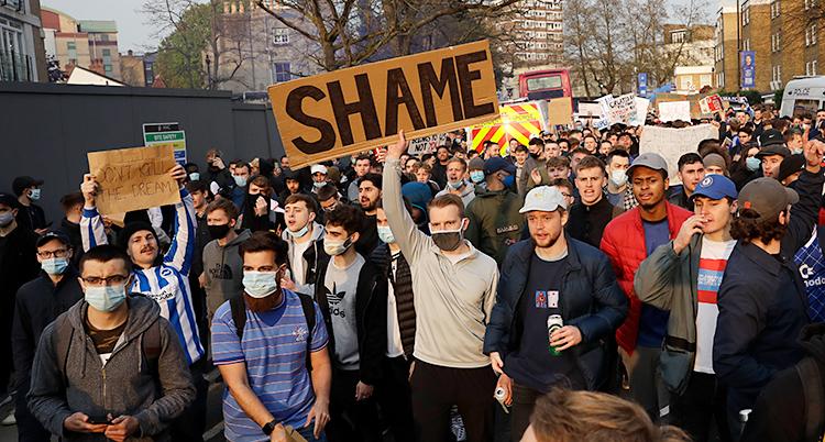 En bild från staden London. Många unga män har samlats ute på gatan. De protesterar. Flera av dem har plakat med sig.