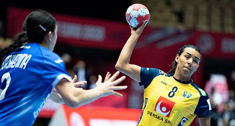 Från en match i handboll. En kvinna i Sveriges lag håller i bollen. Hon hoppar med bollen och ska skjuta ett skott. Hon har en gul tröja. En motståndare står bredvid. Hon har en blå tröja.
