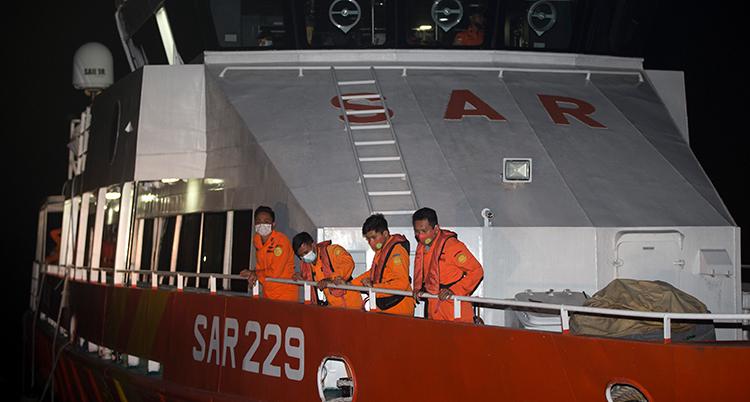 flera besättningsmän på en båt tittar ner i havet.