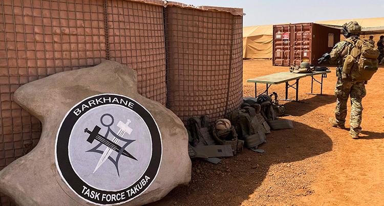 en soldat går vid en byggnad i öknen i Mali.