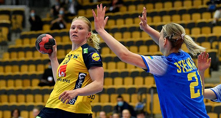 Från en match i handboll. En kvinna med gul kvinna håller bollen i sin högra hand. En kvinna med blå tröja försöker stoppa henne.