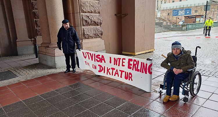 Två personer är utanför riksdagens hus. En av dem sitter i rullstol. De håller i ett plakat där det står Utvisa inte Erlin till en diktatur.