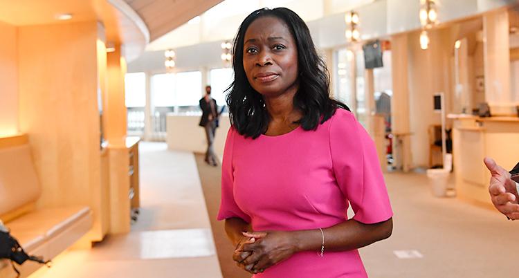 Nyamko Sabuni står i riksdagens hus. Hon tittar mot kameran. Hon har på sig en rosa klänning.