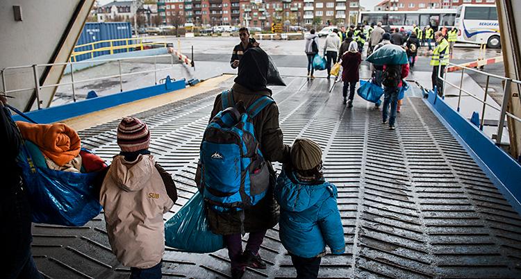 Bilden är från hamnen i Trelleborg. Några personer går av en båt. Det är några vuxna och några barn. Vi ser dem bakifrån.