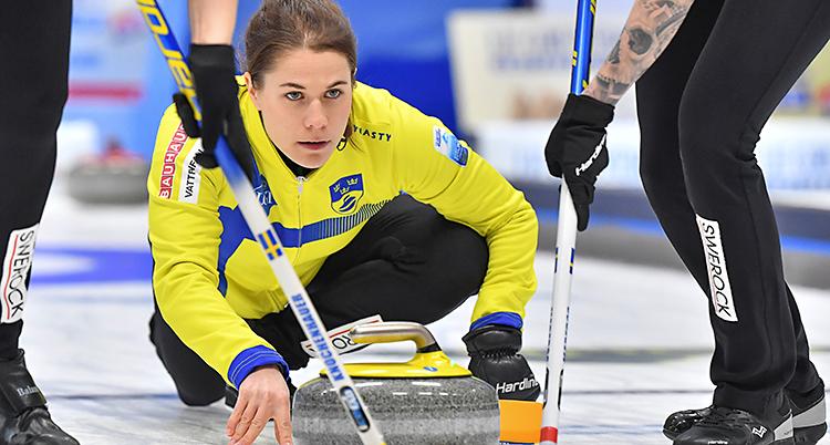 Från en match i curling. Anna Hasselborg skickar iväg en sten. Två andra sopar framför stenen.