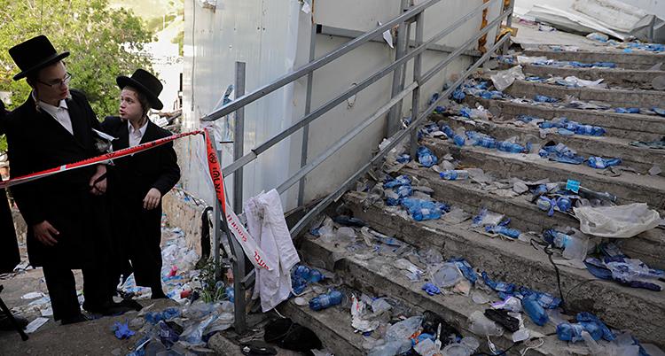 Bilden visar en trappa. Det ligger en massa skräp i trappan. Det ser ut att ha varit kaos. Två personer står och tittar på trappan.