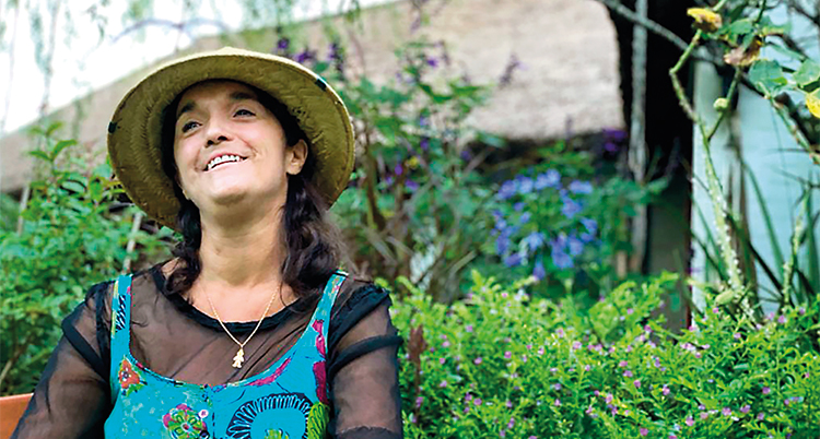 Hon sitter i en grön trädgård. Hon ler och tittar ut ur bilden.
