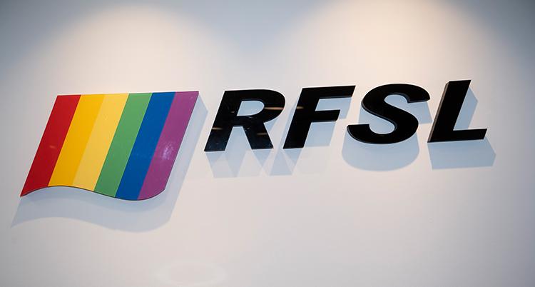 En vägg som det står RFSL på. Bredvid syns en flagga i regnbågens färger. Det är prideflaggan.
